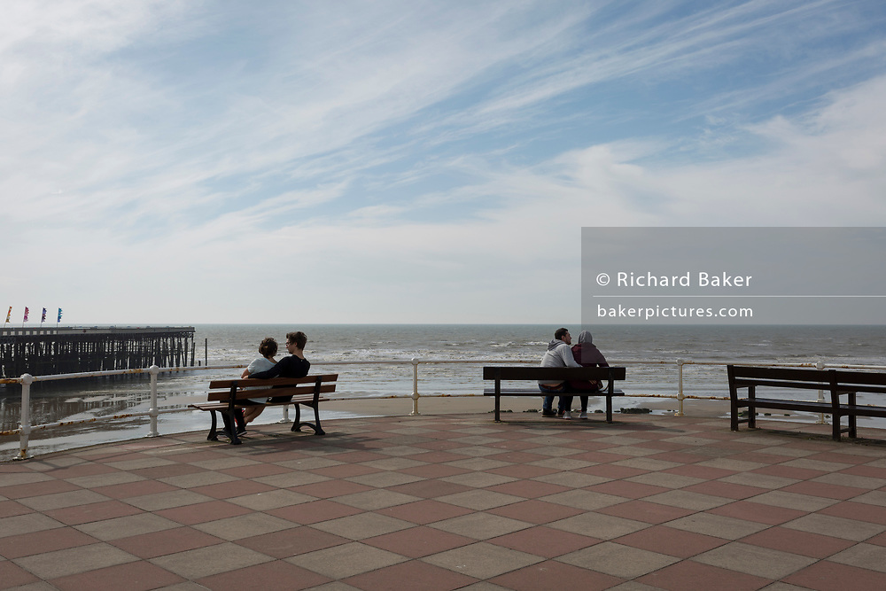 Two romantic couples sit cuddling on benches overlooking the sea and Hastings Pier, on 29th April 2017, at Hastings, East Sussex, England.