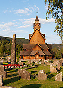 "A stone monolith and cemetery headstones rise at Heddal stave church, Norway's largest stave church. This triple nave stave church, which some call ""a Gothic cathedral in wood,"" was built in the early 13th century and restored in 1849-1851 and the 1950s. Heddal stavkirke is in Notodden municipality, Telemark County, Norway."