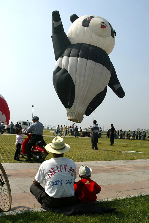 Onlookers watch as a giant panda hot air balloon is inflated during a balloon festival in Shangdong, China,; May 29, 2006. Credit:SNPA / Rob Tucker