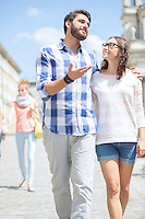Man talking to woman while walking on street