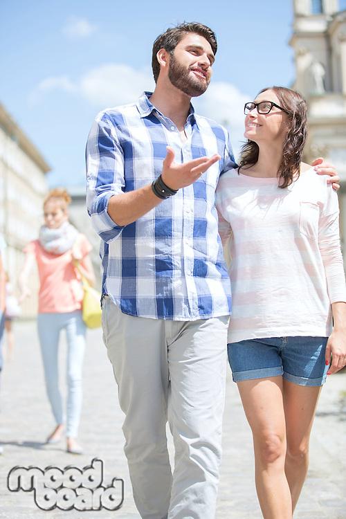 Man talking to woman while walking on street