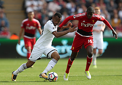 """Swansea City's Jordan Ayew and Watford's Abdoulaye Doucoure battle for the ball during the Premier League match at the Liberty Stadium, Swansea. PRESS ASSOCIATION Photo. Picture date: Saturday September 23, 2017. See PA story SOCCER Swansea. Photo credit should read: David Davies/PA Wire. RESTRICTIONS: EDITORIAL USE ONLY No use with unauthorised audio, video, data, fixture lists, club/league logos or """"live"""" services. Online in-match use limited to 75 images, no video emulation. No use in betting, games or single club/league/player publications"""