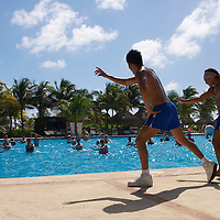 Two resort employees lead a water aerobics class for resort guests.