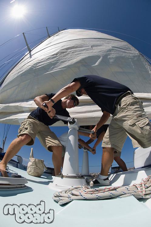 Sailors operating windlass on yacht low angle view wide angle lens