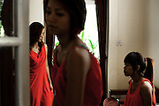 YANGON,MYANMAR,MARCH 2012: Ha Moon, Wai Hnin and Kimmi trying on their stage dresses.<br /> Burma is a country in Transition. And if that hasn't been made clear enough by the political debates and the recent by-elections, meet the Me N Ma Girls, the first girlband in the country.<br /> The timing couldn't be better. After the April 1st elections in 2012 an always increasing number of investors from all over the world has been visiting Myanmar. After decades of military regime and isolation, the strings of censorship have started loosening up. The government censors in fact for years have banned songs and articles, deleting anything that was seen as &quot;to provocative&quot; such as leather outfits and colored wigs.<br /> Describing themselves as Myanmar's first all-girl group, under the management of the Australian dancer and choreographer Nicole May, these five women - coming from either Buddhist or Catholic background and formerly known as Tiger Girls - not only have been challenging censorship laws but they're as well trying to win hearts in a society that in many ways remains man-dominated and socially conservative.<br /> In a country that has been locked up for years, the Me N Ma Girls, embracing western pop culture with skimpy outfits and catchy songs, show with every performance the will of the Burmese youth to come out of a decades-long isolation.<br /> Five girls leading a new form of rebellion: the kind that questions roles and cultural norms.