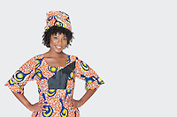 Portrait of young woman in African print attire standing with hands on hips over gray background