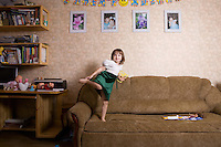 Young girl jumps on sofa