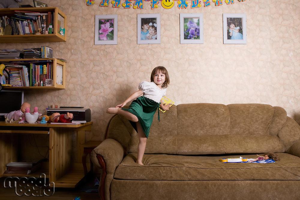 Young girl jumps on sofa
