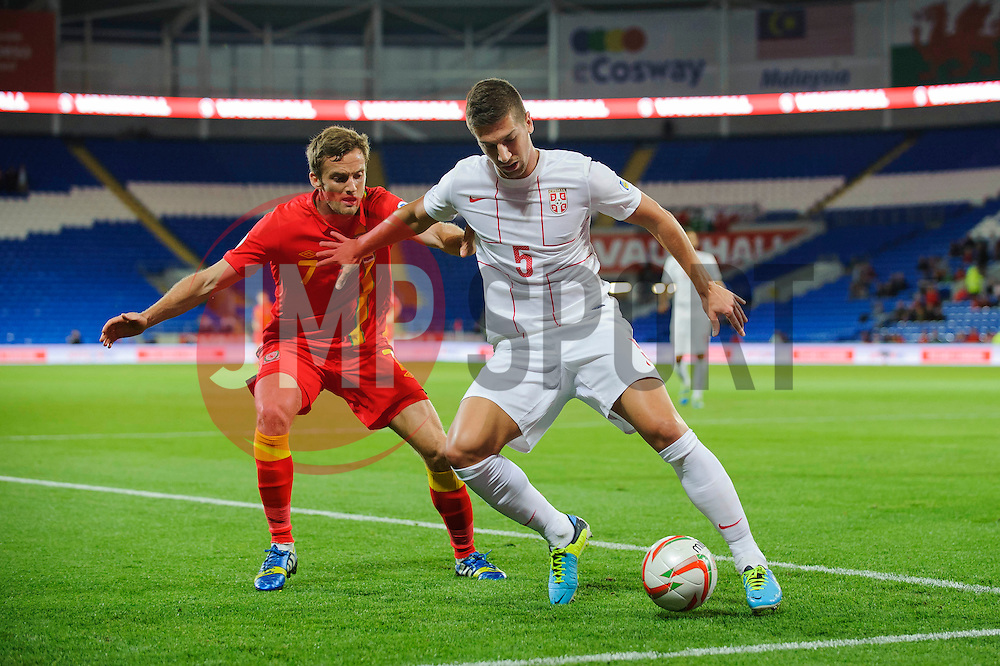 Matija Nastasic of Serbia (Manchester City) is challenged by Andy King of Wales (Leicester City) during the first half of the match - Photo mandatory by-line: Rogan Thomson/JMP - Tel: Mobile: 07966 386802 10/09/2013 - SPORT - FOOTBALL - Cardiff City Stadium - Cardiff -  Wales V Serbia- World Cup Qualifier.