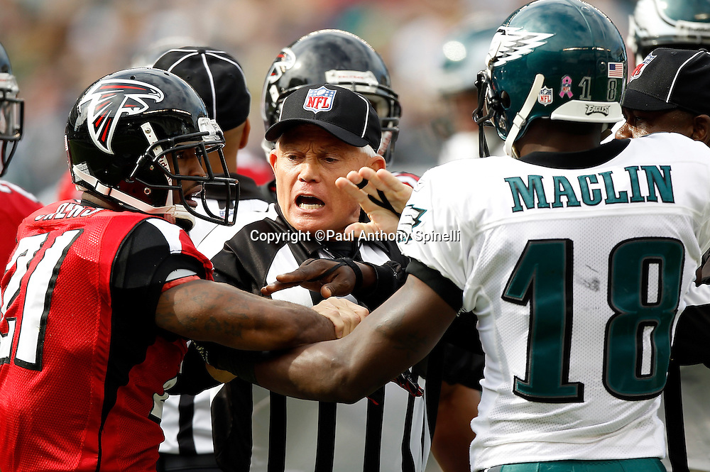 An NFL official breaks up an altercation between Philadelphia Eagles wide receiver Jeremy Maclin (18) and Atlanta Falcons cornerback Christopher Owens (21) during the NFL week 6 football game against the Atlanta Falcons on Sunday, October 17, 2010 in Philadelphia, Pennsylvania. The Eagles won the game 31-17. (©Paul Anthony Spinelli)