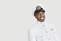 Portrait of a young African American US Navy officer smiling over gray background
