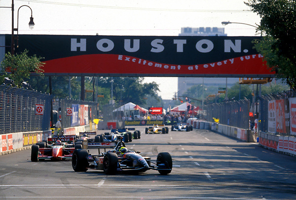 Stock photo of a line of cars coming to a turn in the track at the Houston Texaco Grand Prix.