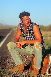good looking man sitting on a suitcase on the side of a road in the desert