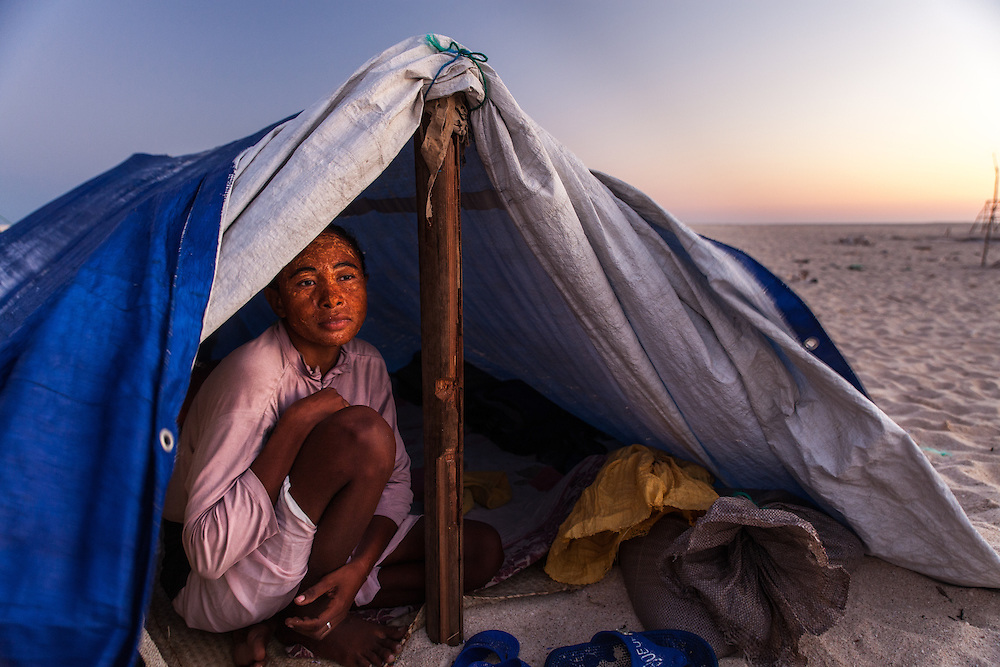 A migrant Vezo lady takes shelter from the wind in her tent.  She camps here on this sand cay with her child and husband for much of the year, returning home to Morombe, 500 km south, only when the cyclone season makes staying here too dangerous.  She prefers life on the islands to living on the mainland because here they can save money and get by, which they can't in her home town.  She aims to save enough money to build a proper house and start her own small business in Morombe.