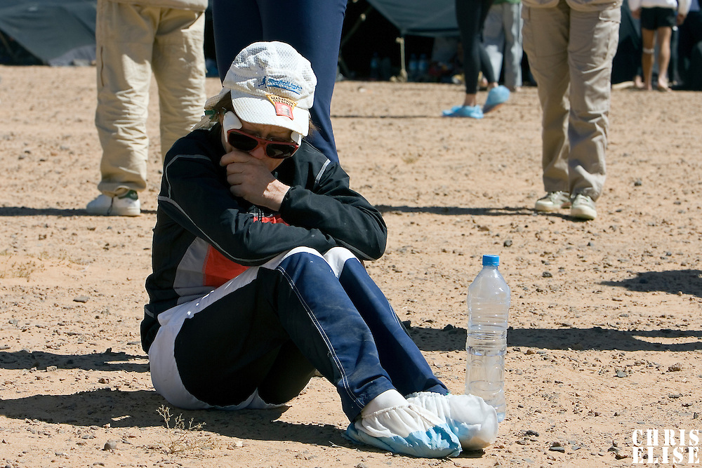 29 March 2007: A runner sits on the ground and cries as she listens to Race Director Patrick Bauer while he informs the participants and the organisation of the death of #53 Bernard Julé of France at 06H35. Bernard Julé was found unconscious by his tent-mates at 6H30 this morning. The organisation's medical team was called immediately and confirmed his death. Bernard Julé died after fourth and longest stage of the 22nd Marathon des Sables between jebel Zireg and west of Kfiroun (43.8 miles). The Marathon des Sables is a 6 days and 151 miles endurance race with food self sufficiency across the Sahara Desert in Morocco. Each participant must carry his, or her, own backpack containing food, sleeping gear and other material.