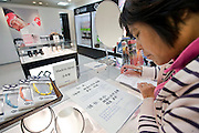 A shopper from China looks at literature written in Mandarin about Arc Quest Co.'s Colantotte line of health and wellness products sold inside Matsuzakaya department store in the Ginza district of Tokyo, Japan on Tuesday 16 Nov. 2010..Photographer: Robert Gilhooly