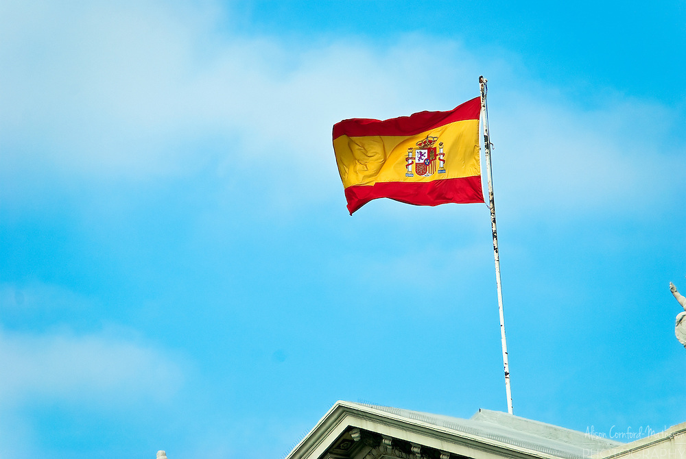 The Spanish flag flies over a building in Barcelona, Spain.