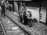 17 DECEMBER 2018 - BANGKOK, THAILAND: A family rides their motorcycle next to railroad tracks near the Sukhumvit Road tourist district in central Bangkok. According to Credit Suisse Global Wealth Databook 2018, which surveyed 40 countries, Thailand has the highest rate of income inequality in the world. In 2016, Thailand was third, behind Russia and India. In 2016, the 1% richest Thais (about 500,000 people) owned 58.0% of the Thailand's wealth. In 2018, they controlled 66.9%. In Russia, those numbers went from 78% in 2016, down to 57.1% in 2018. The Thai government disagreed with the report and said the report didn't take government anti-poverty programs into account and that Thailand was held to an unfair standard because most of the other countries in the report are developed countries in the Organisation for Economic Co-operation and Development.     PHOTO BY JACK KURTZ