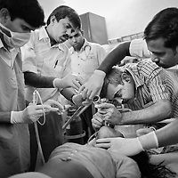 Dr. Yogesh Jain (2nd left), Dr. Raman Kataria (in stripped shirt) and other medical staff at the JSS hospital in Ganiyari, provide emergency medical treatment for a 30-year old woman experiencing seizures after attempting suicide by drinking insecticide. The woman is one of many such suicide cases treated at the JSS hospital in Ganiyari. She was brought to the hospital on a motorbike. After stabalising her, the JSS doctors admitted her to the ICU at the large government hospital in Bilaspur, 25km away. The woman survived thanks to the efforts of the JSS and was discharged from hospital one week later. <br />