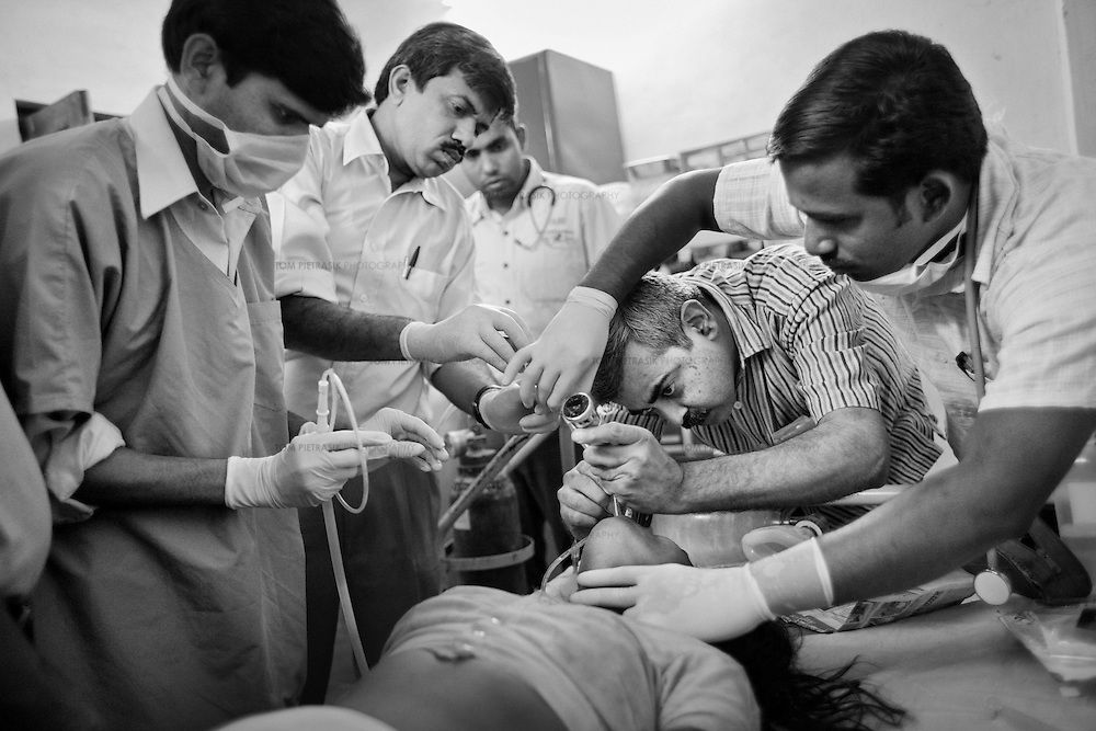 Dr. Yogesh Jain (2nd left), Dr. Raman Kataria (in stripped shirt) and other medical staff at the JSS hospital in Ganiyari, provide emergency medical treatment for a 30-year old woman experiencing seizures after attempting suicide by drinking insecticide. The woman is one of many such suicide cases treated at the JSS hospital in Ganiyari. She was brought to the hospital on a motorbike. After stabalising her, the JSS doctors admitted her to the ICU at the large government hospital in Bilaspur, 25km away. The woman survived thanks to the efforts of the JSS and was discharged from hospital one week later. <br /> <br /> The JSS (Jan Swasthya Sahyog or People's Health Support Group) is a public-health initiative established in 1996 by a handful of committed doctors, all of whom trained at elite medical schools in India. While many of their peers secured high profile, high earning posts in premier hospitals in India, the US and the UK, the doctors at JSS provide a service for poor and marginalised rural communities in Bilaspur district in the eastern India.<br /> <br /> The JSS operate out of a hospital in Ganiyari, near Bilaspur. Relying on grants and donations, the JSS provide a first-class service for a community that would otherwise rely on underfunded and poorly resourced government facilities. Though JSS hospital boasts 30 beds, two operating theatres, a fully-equipped lab and three outpatient clinics a week, the service provided by JSS is over-subscribed by a community of 800,000 people from 1,500 villages. <br /> <br /> The JSS offers training on new agricultural techniques. The JSS has a well established outreach program of village-clinics and employs over 100 village health workers serving 53 villages. They also operate an ambulance service and assist with transport costs for a community who's access to essential services has been undermined by the Chhattisgarh government's decision to completely disinvest in public transport. <br /> <br /> Photo: Tom Pietrasik<b