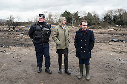 © Licensed to London News Pictures. Calais, France. 02/03/16. With a police escort, Calais Prefect Fabienne Buccio (centre) surveys progress made on the third day of the demolition of the Calais 'Jungle' camp. French authorities have begun clearing the southern half of the camp, which charities estimate to contain some 3,500 people. Photo credit: Rob Pinney/LNP