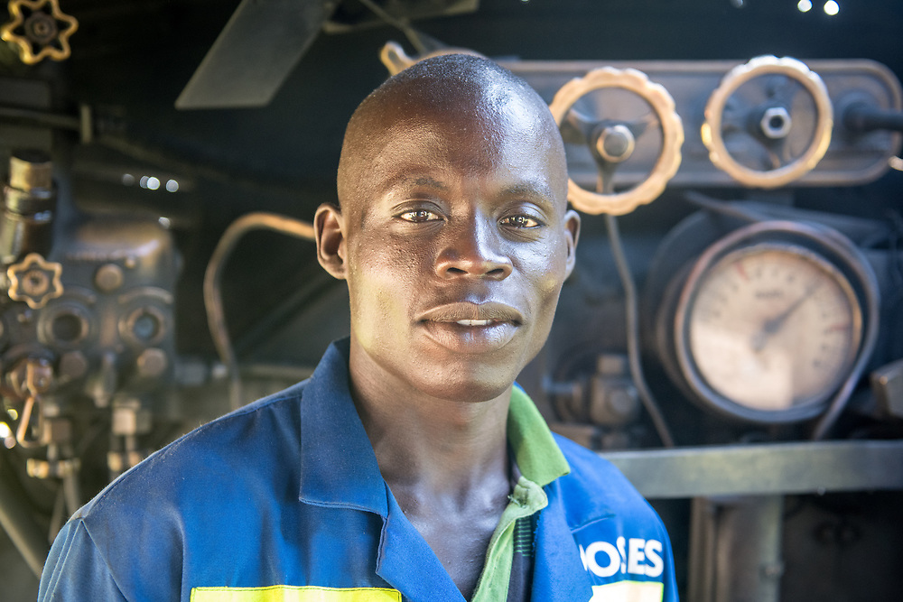 A close up of an adult male worker in front of a Garratt steam locomotive Zimbabwe