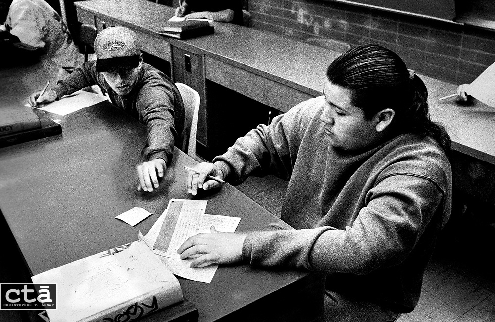 "Because his grades were not high enough the year before, Chunk was cut from the football team. He has worked to raise his marks, but often resorts to cheating. A classmate passes him a crib note during a biology quiz. ""Every test I get his answers, but change them a little so the teacher won't know,"" he said."