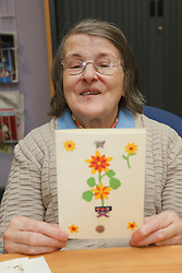 Person displaying their craft activity at a resource for people with physical and sensory impairment.