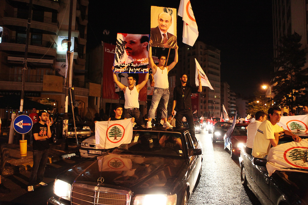 "As the results started to come out from Lebanon's general elections, the Beirut 1 district appeared to be swept by Christian groups from the pro-western ""March 14"" alliance. As exit polls projected the win for March 14, supporters of the Lebanese Forces and Phalange parties came out to the Ashrafiyeh neighborhood's Sassine Square to celebrate. At around 1am Nadim Gemayel made a suprise appearance and briefly addressed supporters. Nadim Gemayel is the son of the Phalange party founder, Pierre Gemayel. Nadim's father, Bashir was assasinated in 1982 during the Lebanese civil war and remains one of the most popular icons of many of the Lebanon's Maronite Christians. The 27-year-old Nadim Gemayel will be one of Lebanon's youngest parliamentarians. The celebrations at Sassine were one of Lebanon's first celebrations after the elections ended on 7 June. ///Celebrators hold images of Lebanese Forces leader Samir Geagea at Sassine Square in Beirut."
