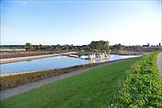 Nederland, Nijmegen, 15-9-2015De nevengeul aan de overkant van de Waal bij Lent nadert zijn voltooiing. Laatste werkzaamheden. Aan de kant van de drempel, de inlaat, werkt een zandzuiger om de geul op diepte te krijgen. Grootste onderdeel van de vele werken van Rijkswaterstaat om bij hoogwater een betere waterafvoer in de rivier te hebben. Het is een omvangrijk project waarbij onder meer de pijlers van het spoorviaduct een bredere basis kregen omdat die straks in de loop van het water staan. Ook de n325 die vanaf de Waalbrug naar Arnhem loopt is over 400 meter opnieuw aangelegd omdat het talud vervangen wordt door een nieuwe brug met drie gracieuze pijlers. Het dorp veurlent komt op een kunstmatig eiland te liggen met twee bruggen als ontsluiting. Een voetgangersbrug en een andere, de Promenadebrug, voor normaal verkeer. Inmiddels begint de nieuwe kade aan de noordkant van deze geul vorm te krijgen. Ruimte voor de rivier, water, waal. In de nieuwe dijk wordt een drempel gebouwd die stapsgewijs water doorlaat en bij hoogwater overloopt.The Netherlands, NijmegenMeasures taken by Nijmegen to give the river Waal, Rhine, more space to flow during highwater and to prevent the risk of flooding. Room for the river. Reducing the level, waterlevel. Large project to create a new paralel gully, an extra flow of water, so the river can drain more water during highwater. Due to climate change and expected rise, increase of the sealevel, the Dutch continue to protect their land from the water.Foto: Flip Franssen/HH