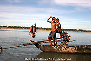 Three boys use an old fishing boat as a diving platform in Kratie, Cambodia. Kratie is the home of the world famous but nearly extinct Irrawaddy dolphin, the only surviving fresh water dolphin in the world that inhabits the Mekong river 10 miles north of this point.