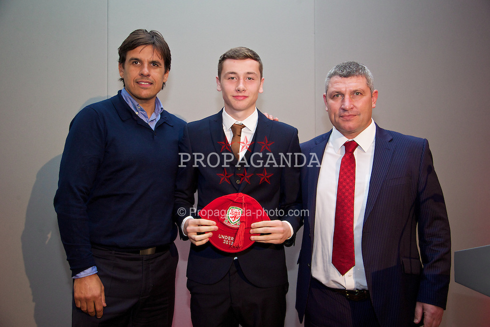 CHEPSTOW, WALES - Saturday, May 24, 2014: Rhys Williams is presented with his Wales Under-16's cap by Senior mens' team manager Chris Coleman and coach Osian Roberts at the St. Pierre Marriott Hotel & Country Club. (Pic by David Rawcliffe/Propaganda)