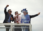 © Licensed to London News Pictures. 01/06/2012. Epsom , UK Men pose on top of a double decker bus with a cardboard cutout of HRH Queen Elizabeth. Ladies Day today 1st June 2012 at Epsom 2012 Investic Derby Festival. The Queen will attend tomorrow's race meet as part of the 60th Jubilee celebrations. Photo credit : Stephen Simpson/LNP