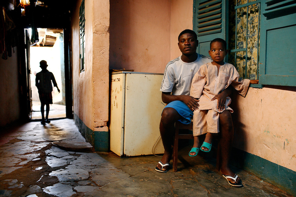 Christian Nankap, 17 in his family home, with his nephews Jean 3 years old on his lap and Frank, 6 years old in the door.<br /> Christian Nankap, 17 years old is a young talented player in Yaounde. He is about to go to Florida, USA to train on FC Orlando's training program. If he is as good as they hope the club plans to sell him to a European club when he turns 18. Christian's family lost a lot of money when a rogue agent offered to bring Christian's older brother to Europe and then disappeared with the money. A lot of expectations hangs on Christian's shoulders.