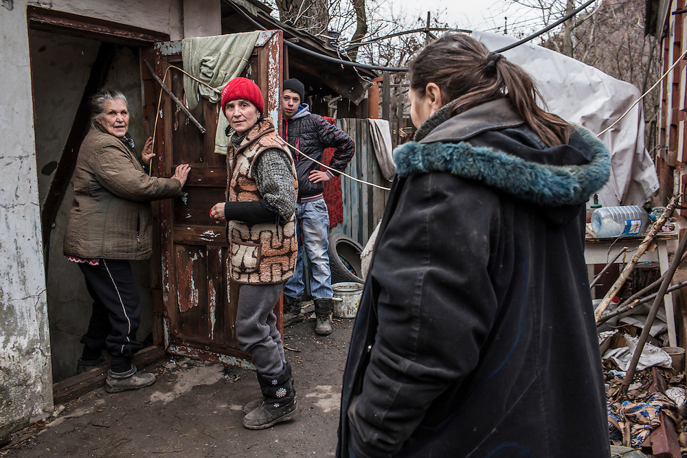 DONETSK, UKRAINE - FEBRUARY 3, 2015: Neighbors Alla Kozikova, 81, Valentina Anosikova, 53, Danyl Vasylenko, and Vera Dmitrenko, 67, from left, go back into the basement shelter in which they've been living for days at the sound of nearby shelling in the Petrovsky district of Donetsk, Ukraine. The neighborhood has been under heavy shelling for the past four days, and a brief pause allowed a few residents to leave their basement hiding places for some fresh air. CREDIT: Brendan Hoffman for The New York Times