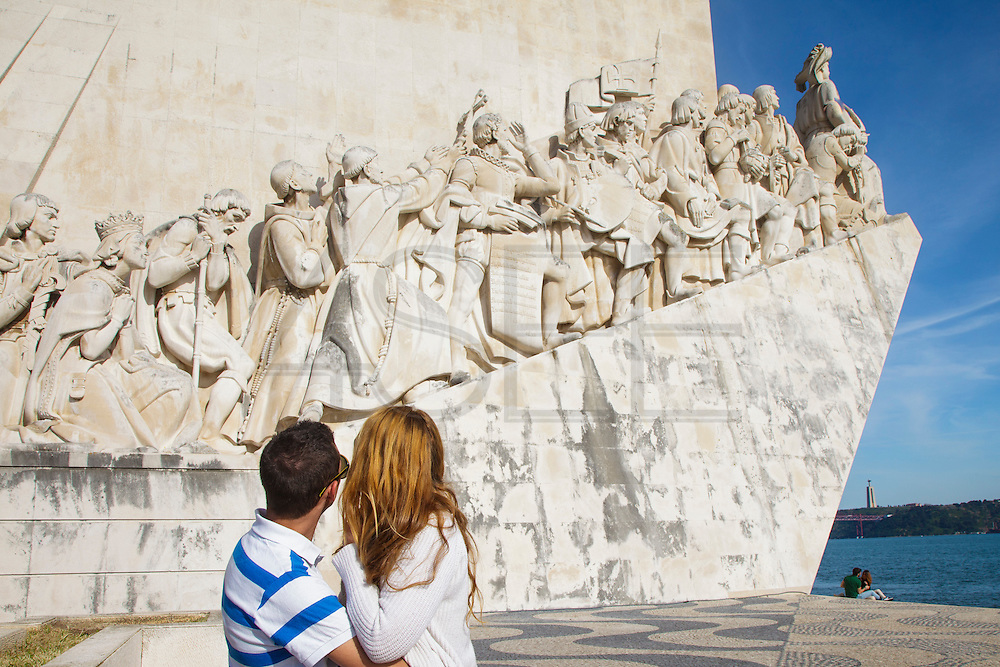 A couple enjoying Tagus riverside near to the Discoveries Monument in Lisbon. Located along the river were ships departed to explore and trade with India and Orient, the monument celebrates the Portuguese Age of Discovery (or Age of Exploration) during the 15th and 16th centuries and it was Inaugurated on 9 August 1960, its completion was one of several projects nationwide intended to mark the Comemorações Henriquinas (the celebrations marking the anniversary of the death of Henry the Navigator).