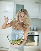 Portrait of happy woman mixing salad in kitchen