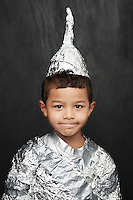 Portrait of young boy (5-6) in aluminum foil knight costume studio shot