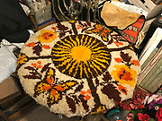 Hand made by preacher &ndash;kitchen table from front of grocery with hook rug top and card board decorative supports on casters and spins. Rug has butterfly design0has foil and bears and tape and beads 32in tall by 34 in diameter <br />