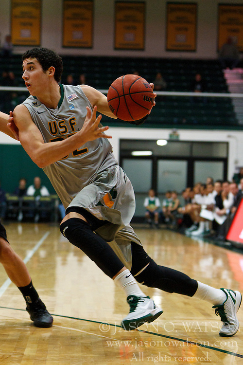 Dec 10, 2011; San Francisco CA, USA;  San Francisco Dons forward Angelo Caloiaro (32) dribbles the ball against the Pacific Tigers during the first half at War Memorial Gym.  San Francisco defeated Pacific 79-69. Mandatory Credit: Jason O. Watson-US PRESSWIRE