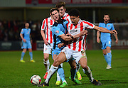 Dominic Ball is tackled by Troy Brown during the Sky Bet League 2 match between Cheltenham Town and Cambridge United at Whaddon Road, Cheltenham, England on 14 April 2015. Photo by Alan Franklin.