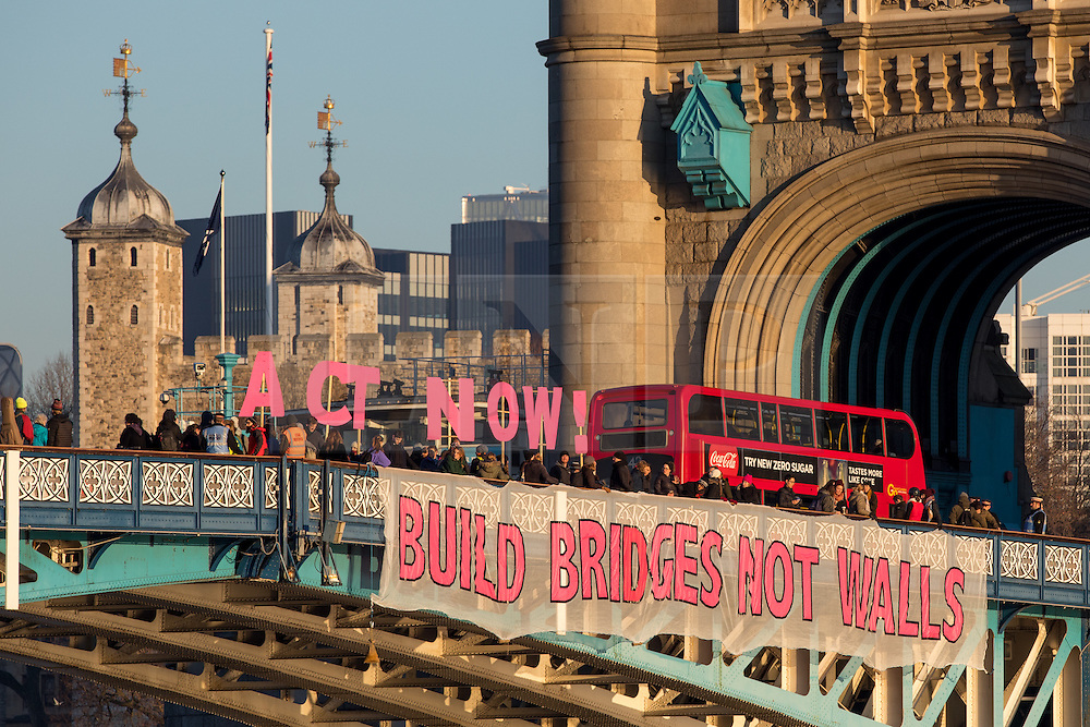 © Licensed to London News Pictures. 20/01/2017. London, UK. A banner is dropped from Tower Bridge reading 'Build Bridges not Walls', on the day Donald Trump becomes president of the United States of America. The slogan is in reference to Trump's campaign to build a wall on the border between USA and Mexico. Photo credit : Tom Nicholson/LNP