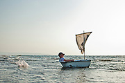 Man in a bathtub like boat with a sail in the sea