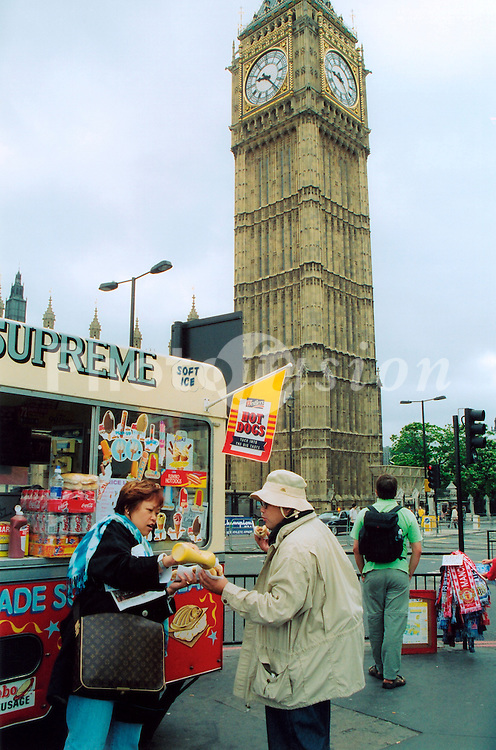Japanese tourists buying hot dogs from fast food van in front of Big Ben London UK