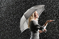 Businesswoman sticking hand out from under umbrella during rain side view