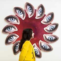 "© Licensed to London News Pictures. 25/09/2019. LONDON, UK. A staff member poses with ""Look me in the eyes, tell me what you see"", 2019, by Sarra Badel at the preview of START, a contemporary art fair comprising eclectic works from a variety of international emerging artists.  The fair takes place at the Saatchi Gallery in Chelsea 26 to 29 September 2019.  Photo credit: Stephen Chung/LNP"