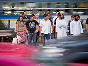 29 FEBRUARY 2008 -- BANGKOK, THAILAND:   Thais and a group of Moslem men wait to cross Sukhumvit Road in heavy traffic in Bangkok, Thailand.  Photo by Jack Kurtz/ZUMA Press