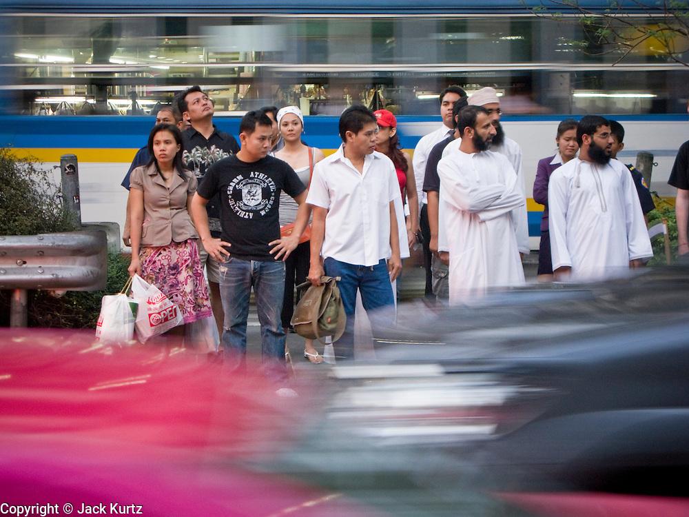 29 FEBRUARY 2008 -- BANGKOK, THAILAND:   Thais and a group of Moslem men wait to cross Sukhumvit Road in heavy traffic in Bangkok, Thailand.  Photo by Jack Kurtz/ZUMA Press