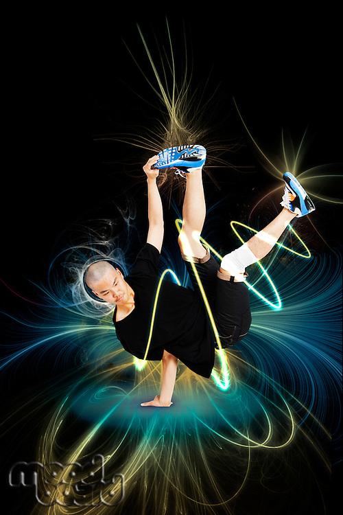 Break dancer performing handstand over abstract black background