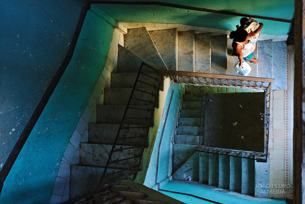 Mother and child going down the stairway of a building at Vedado